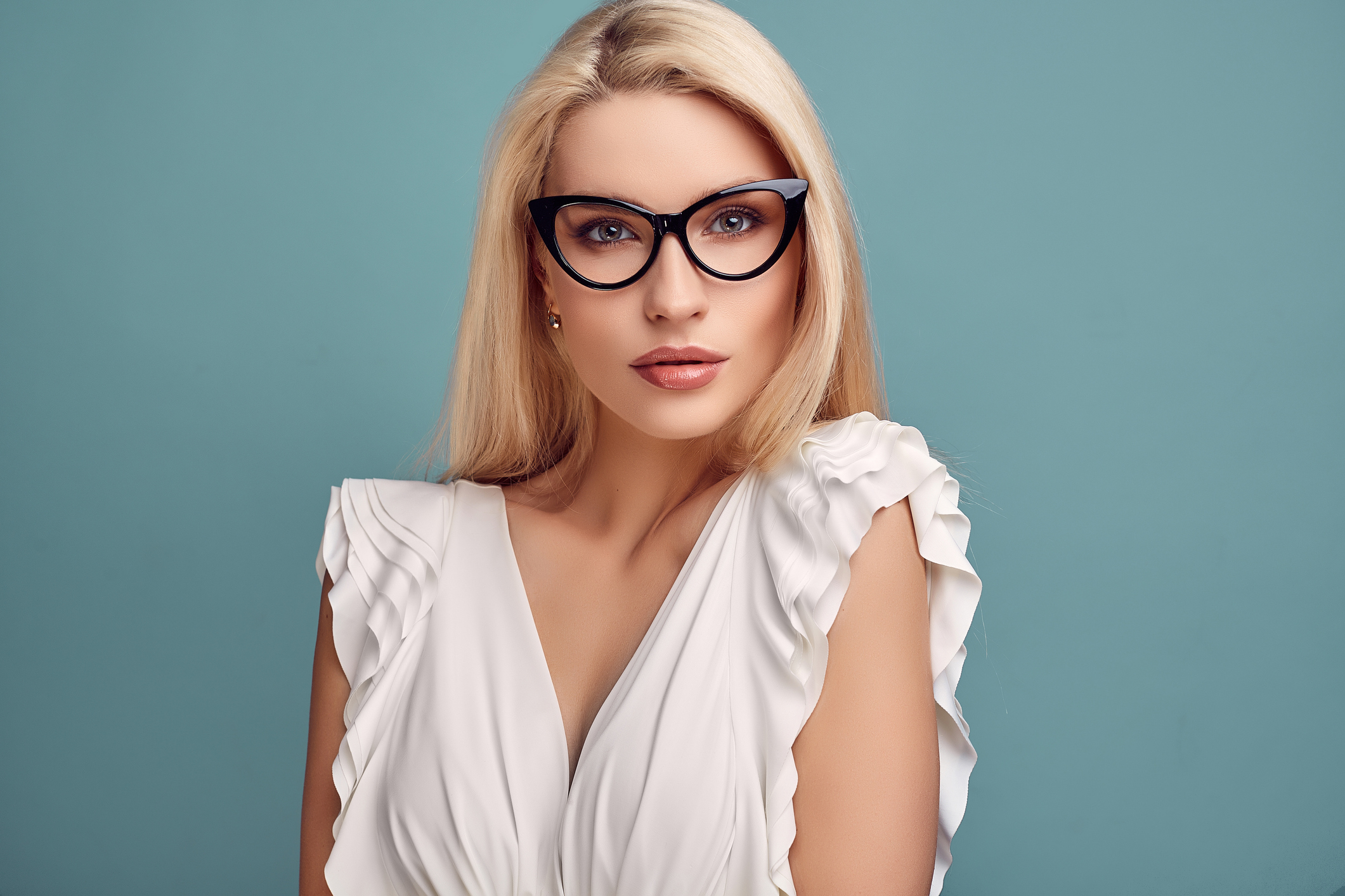 Portrait of gorgeous sensual blonde woman in fashion white dress and glasses posing on blue background in studio